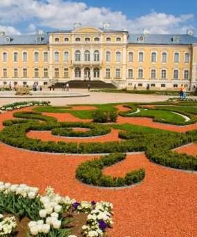 Gele barokke paleis met tuin op voorgrond